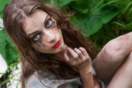 Beautiful young dirty mad and manic looking girl wearing torn clothes and smeared with mud and dried blood frightenedly looks up in the forest. Copy space. Concept design. Фото со стока