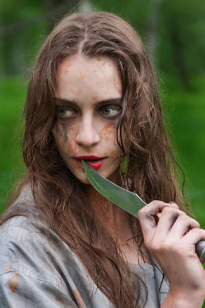 Beautiful young dirty mad and manic looking girl wearing torn clothes and smeared with mud and dried blood touches the face with a knife in the forest. Copy space. Concept design. Фото со стока