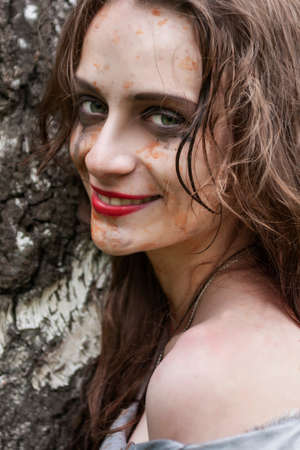 Beautiful young dirty smiling mad and manic looking girl wearing torn clothes and smeared with mud and dried blood stands and huddles to a tree in the forest. Copy space. Concept design.