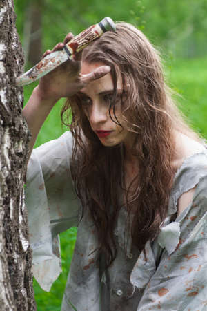 Beautiful young dirty mad and manic looking girl wearing torn clothes and smeared with mud and dried blood holds her hand to the knife stuck into tree in the forest. Copy space. Concept design. Stock Photo