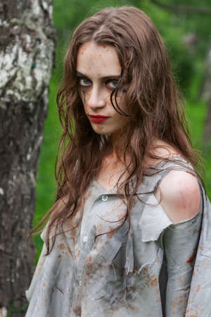 Beautiful young dirty sullen mad and manic looking girl wearing torn clothes and smeared with mud and dried blood stands in the forest. Copy space. Concept design.
