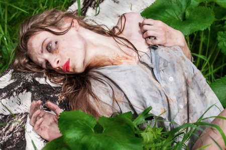 Beautiful young dirty mad and manic looking girl wearing torn clothes and smeared with mud and dried blood lies on the trunk of a fallen tree in the forest. Copy space. Concept design.