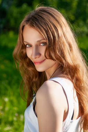 Beautiful smiling young girl model wearing a dress in sunlight. Close up portrait. Lifestyle photo. Advertising, commercial and fashion design. Copy space. Фото со стока