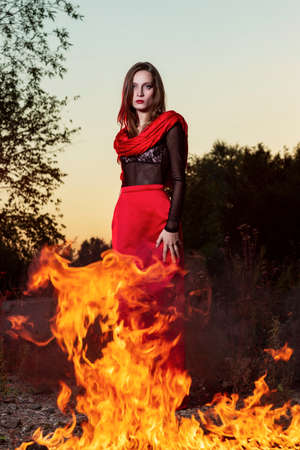 Beautiful fashion model girl wearing a red long skirt and a red shawl stands near the big fire in sunset. Conceptual, fashionable, modern and advertising design.