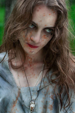 Beautiful young dirty mad and manic looking girl wearing torn clothes and smeared with mud and dried blood looks crazy wild sideways in the forest. Copy space. Concept design. Фото со стока