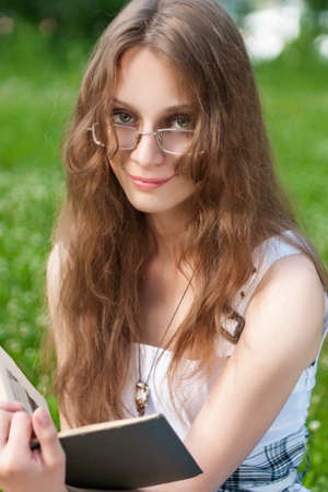 Beautiful young student girl model wearing a dress and glasses sits on a meadow with a book in sunny weather. Lifestyle photo. Advertising, educational design. Copy space.