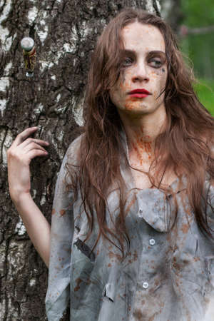 Beautiful young dirty mad and manic looking girl wearing torn clothes and smeared with mud and dried blood stands and huddles to a tree in the forest. Copy space. Concept design. Фото со стока