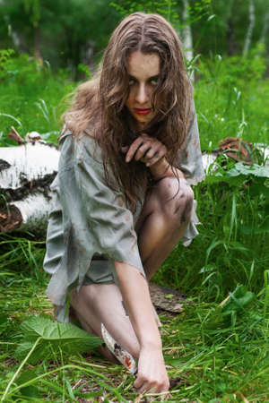 Beautiful young dirty mad and manic looking girl wearing torn clothes and smeared with mud and dried blood steals with a knife in her hand in the forest. Copy space. Concept design.