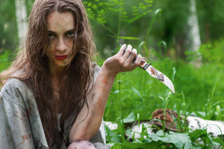 Beautiful young dirty mad and manic looking girl wearing torn clothes and smeared with mud and dried blood holds a knife in her hand in the forest. Copy space. Concept design. Фото со стока