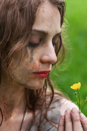 Beautiful young dirty mad and manic looking girl wearing torn clothes and smeared with mud and dried blood holds a small field flower in her hands in the forest. Copy space. Concept design.