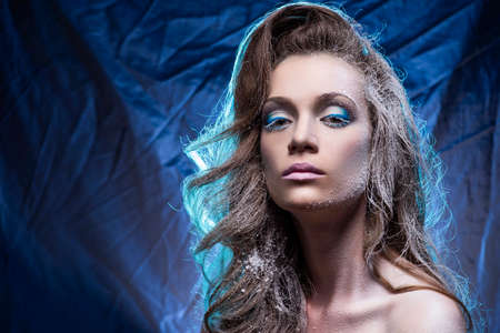Beautiful young long-haired topless model girl with snow-covered skin and hair covers her big breasts with her hands on a blue crumpled background. Cold makeup. Copy space. Advertising design. Фото со стока