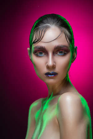 Beautiful young brunette wet model girl with naked shoulders on a pink gradient background. Vanguard conceptual makeup and hairstyle. Healthy clean skin. Copy space. Advertising and commercial design.