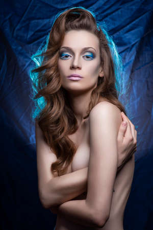 Beautiful young slender long-haired topless model girl, covers her large breasts with her hands on a blue crumpled background. Cold blue makeup. Copy space. Advertising and commercial design.