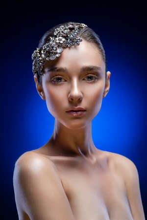 Beautiful young brunette model girl with naked shoulders wearing jewelry diadem on a blue-black gradient background. Golden make-up. Healthy clean skin. Copy space. Advertising and conceptual design.