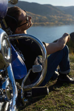 Young man wearing a black leather jacket, sunglasses and jeans sits outdoor on a ground at a motorcycle, resting on a mountain above the river. Lifestyle, travel. Copy space. Advertising design.