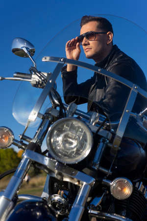 Young man wearing a black leather jacket, sunglasses and jeans sits outdoor on a motorcycle, on a mountain on a blue sky background. Lifestyle, travel. Copy space. Advertising and commercial design. Фото со стока