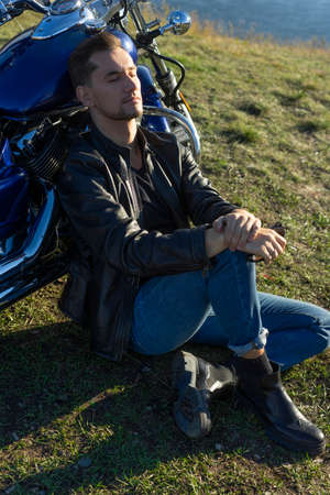 Young man wearing a black leather jacket and jeans sits outdoor on a ground at a motorcycle, resting on a mountain above the river. Lifestyle, travel. Copy space. Advertising design.
