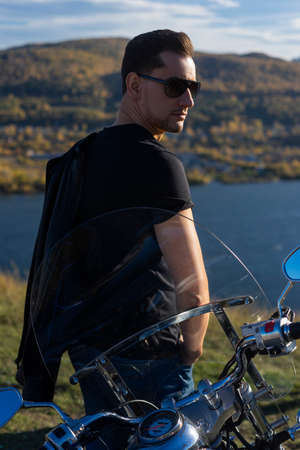 Young man wearing a black leather jacket, sunglasses and jeans stays outdoor at a motorcycle, resting on a mountain above the river. Lifestyle, travel. Copy space. Advertising and commercial design