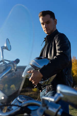 Young man wearing a black leather jacket holds mirror helmet in his hands and rests stays outdoor near a motorcycle. Lifestyle, travel. Copy space. Advertising and commercial design.