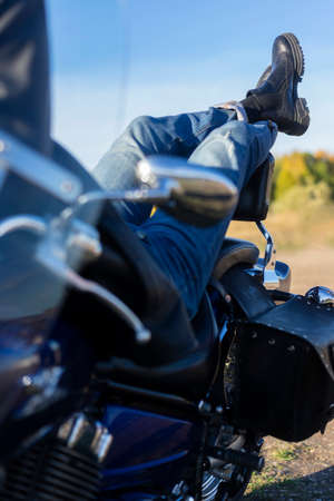 The legs of a young man wearing jeans and boots, lying relaxed on a motorcycle in nature. Close up conceptual photo. Travel, lifestyle. Copy space. Advertising and commercial design
