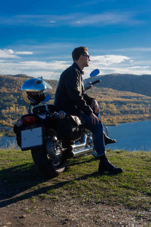 Young man wearing a black leather jacket, sunglasses and jeans sits outdoor on a motorcycle, resting on a mountain above the river. Lifestyle, travel. Copy space. Advertising and commercial design. Фото со стока