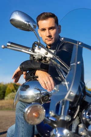 Young man wearing a black leather jacket and jeans sits outdoor on a motorcycle, on a mountain on a blue sky background. Lifestyle, travel. Copy space. Advertising and commercial design.