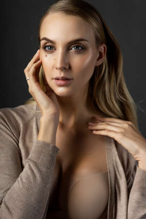 A beautiful blonde girl model wearing a knitted beige dress, unbuttoned on her breasts and a bra touches her face with her hand. Nude makeup. Clean, healthy skin. Gray background. Copy space