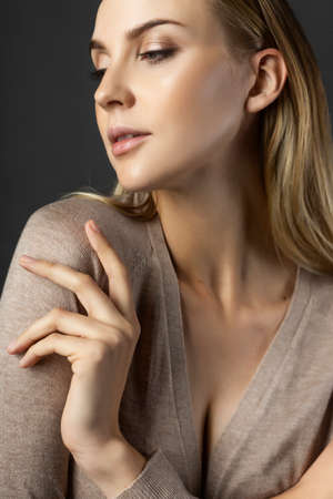 A beautiful blonde girl model wearing a knitted beige dress, unbuttoned on her breasts and a bra touches her shoulder with her hand. Nude makeup. Clean, healthy skin. Gray background. Copy space