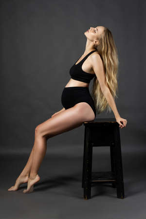 A beautiful pregnant leggy blonde woman wearing a black maternity underwear is sitting with her head thrown back on a chair against a gray background.