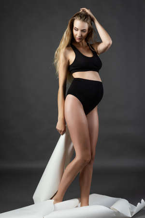 A beautiful smiling young pregnant woman blonde wearing a black maternity underwear is standing on a gray background and tearing a large sheet of white paper. Fashion, health, beauty. Copy space. Standard-Bild