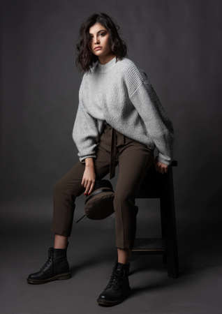 Beautiful brunette girl wearing a casual style sweater, pants, cap and a boots sits on a stool and holds a cap in her hand on a gray background. Nude natural makeup Fashion design. Copy space Фото со стока