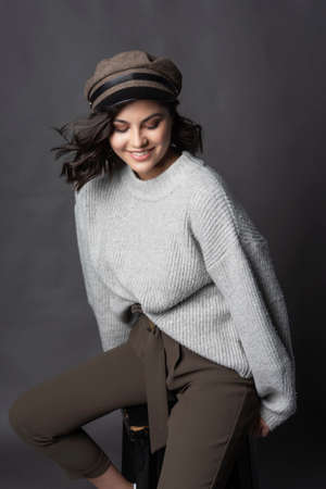 Beautiful brunette girl wearing casual style knitted sweater, brown pants and a hat, sits on a stool on a gray background. Natural nude makeup. Fashion, advertising and commercial design. Copy space. Фото со стока