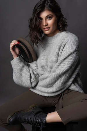 Beautiful smiling brunette girl wearing casual style sweater, pants, cap and a boots sits with her leg up on a stool and holds a cap in her hand on a gray background. Nude natural makeup. Copy space