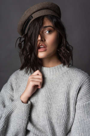 Beautiful scared brunette girl wearing a casual style knitted sweater and cap touches her hair with her hand on gray background.