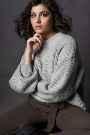 Beautiful brunette girl wearing casual style knitted sweater, brown pants, sits on a stool on a gray background