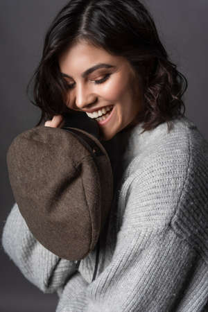 Beautiful smiling brunette girl wearing a casual style knitted sweater bites visor of her cap on gray background.