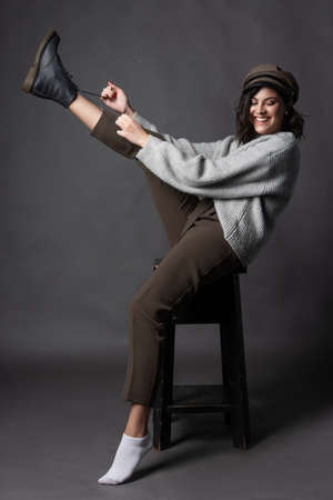 Beautiful smiling brunette girl wearing a casual style sweater, pants and cap puts a shoe on her leg on a gray background.  Fashion, advertising and commercial design. Copy space. Фото со стока