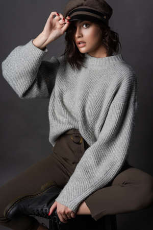 Beautiful surprised brunette girl wearing casual style sweater, pants, cap and a boots sits with her leg up on a stool and holds her hand over the visor on a gray background.