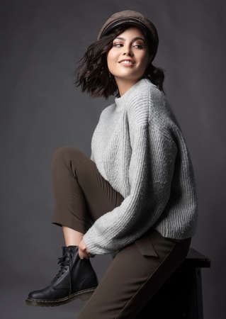 Beautiful smiling brunette girl wearing a casual style sweater, pants and cap puts a shoe on her leg on a gray background.