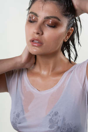 Beautiful wet brunette girl with water drops running down her face, wearing a white translucent T-shirt, through which a black bra shines through. Isolated on white background. Natural makeup. Stockfoto