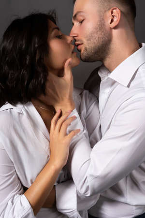 Closeup of a beautiful couple wearing white shirts. The girl and the man passionately almost touch their lips to each other. Casual style. Lifestyle, fashion, commercial design. Gray background.
