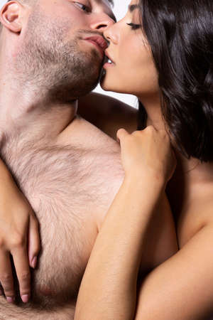 Closeup of a beautiful couple, topless. A man and a girl hug, and they passionately touch each other with their lips. Lifestyle, fashion, love, commercial design. Isolated on white. Copy space. Фото со стока