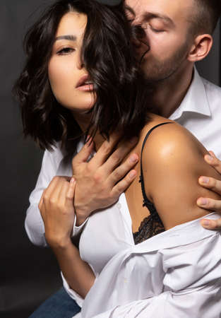 Closeup of a beautiful couple wearing white shirts. A man passionately touches his lips to the girls hair. Casual fashionable style. Lifestyle, love, commercial design. Gray background. Фото со стока