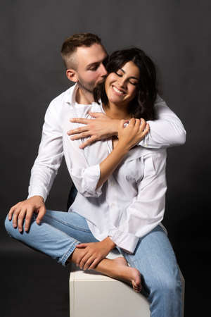 Beautiful couple wearing white shirts and jeans are sitting on a white cube. Man passionately hugs a girl whose shoulder is bare. Casual style. Lifestyle, fashion, commercial design. Gray background. Фото со стока