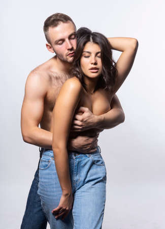 Beautiful couple wearing jeans and topless. Man passionately hugs the girl from behind, covering her big breasts with his hands. Casual style. Lifestyle, fashion, commercial design. Isolated on white.