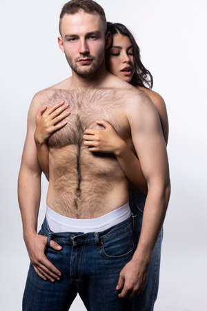 Beautiful couple wearing jeans and topless. The girl sensually hugs the man from behind. Casual fashionable style. Lifestyle, fashion, love, commercial design. Isolated on white.