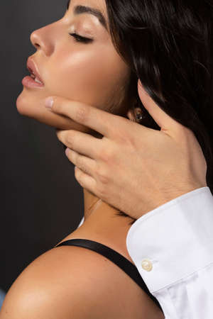 Closeup of a beautiful couple wearing white shirts. A man sensually touches the face of a girl whose shoulder is bare. Casual fashionable style. Lifestyle, fashion, commercial design. Gray background.
