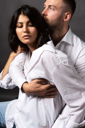 Closeup of a beautiful couple wearing white shirts and jeans. A man passionately hugs a girl. Casual fashionable style. Lifestyle, fashion, advertising and commercial design. Gray background.