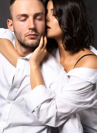 Closeup of a beautiful couple wearing white shirts. The girl passionately touches her lips to the cheek of a man. Casual fashionable style. Lifestyle, fashion, commercial design. Gray background.