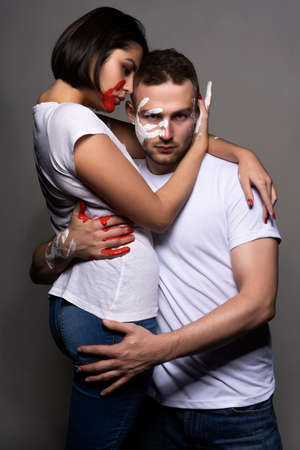 Beautiful couple of artists wearing jeans and white t-shirts soiled with white and red paint sensually hug each other on gray. Palm prints painted on their faces. Concept, fashion design. Copy space Фото со стока